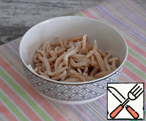 All salad ingredients (except cheese) should be cut into strips. The weight of already cleaned products is given. Boil the squid, cool it, and slice it.
