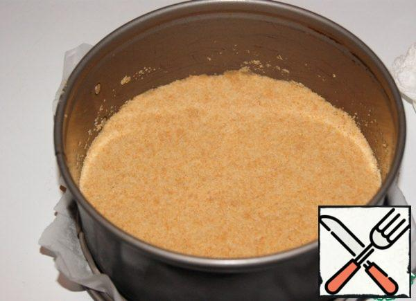 Cookies ground into crumbs. Melt the butter and add to the crumbs and mix well. The bottom of the form is 18 cm. in diameter, cover with baking paper. Line a cookie crumb and tamp it well. Place in the refrigerator.