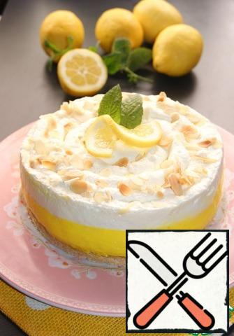 Release the cheesecake from the mold. Cream whisk with vanilla until stable peaks, adding powdered sugar at the very end, so they hold their shape better. Put the cream on top of the cheesecake in a spiral shape and sprinkle with almond petals or crumbled cookies. Garnish with lemon slices and mint leaves.