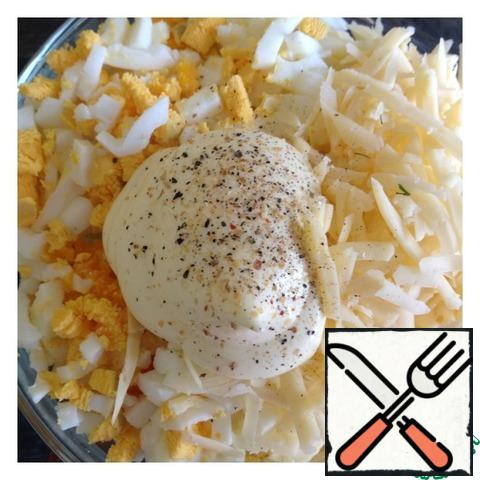 Grate the cheese on a large grater, cut the eggs into cubes. Add spices and mayonnaise. Mix the salad.