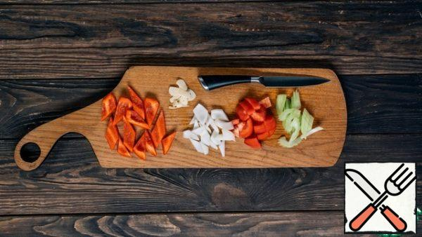 Prepare the vegetables for the stew: coarsely chop the onion and bell pepper, peel and cut the celery into slices, remove the skin from the tomatoes and chop them into cubes.