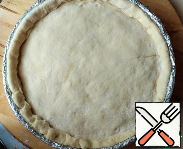 Then roll out a smaller part of the dough and cover the pie. Trim the excess dough and pinch the edges.