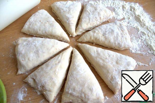 Transfer the remaining dough to the table with flour, slightly flatten into a flat cake, divide into segments.
