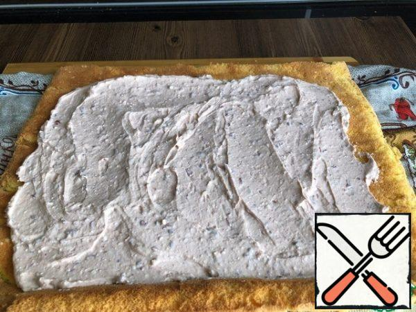 Unfold the cooled biscuit, apply the cream to the entire surface of the biscuit.