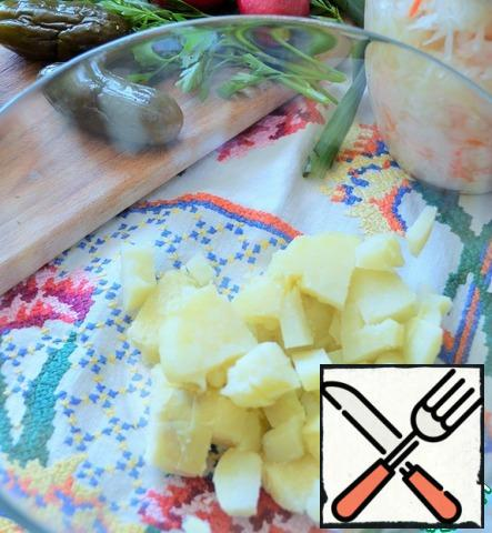 Peel and dice the potatoes.