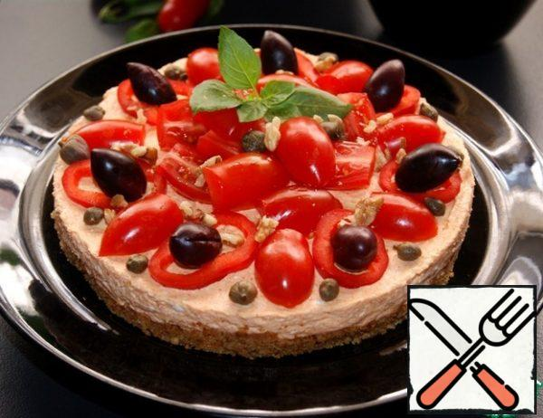 Release the cheesecake from the mold and garnish with rings of pepper, cherry, capers, olives and a sprig of Basil. Sprinkle with nuts.