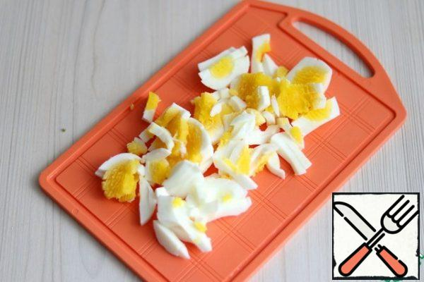 Boil the eggs and cut them into strips.