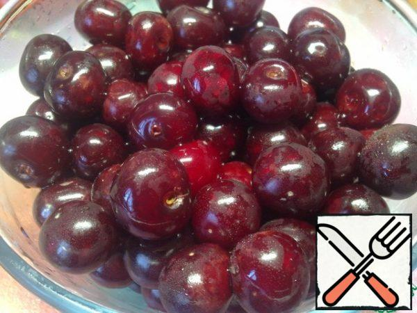 While the syrup cools, prepare the cherries. We sort and remove the spoiled berries, wash them and put them in a colander to drain the water.