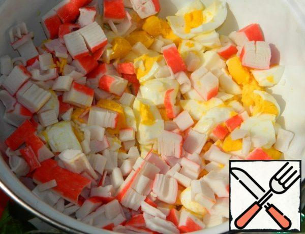 Cut the eggs and crab sticks not quite fine.