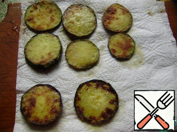 Fried zucchini spread on a paper towel to remove excess oil.