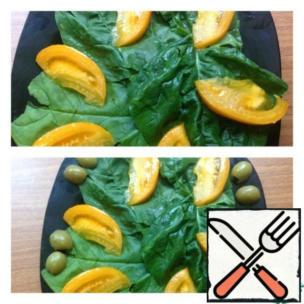 Spinach leaves are washed and dried. We put it on a plate. Cut the tomato into thin pieces and send it to the spinach leaves. Cut the olives in half and put them on a plate.