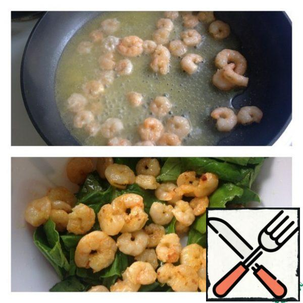 In a hot pan, pour a little oil and the juice of half an orange. Lay out the prawns and fry for 3-4 minutes. In a salad bowl, put the washed and dried spinach leaves, and send the fried prawns to the same place.