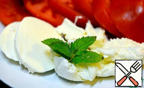 Cut the mozzarella into circles or just tear it with your hands and put it on top of the tomatoes. Garnish with mint and arugula leaves.