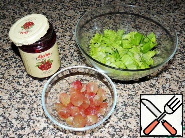 Cut the grapes into halves and remove the seeds (if any). Cut the salad coarsely or tear it with your hands, leave a few leaves for serving. Add the crushed garlic clove and lingonberry sauce, which will give a unique sweet and tart taste.