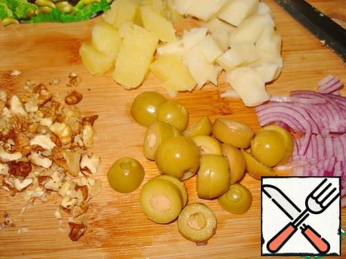Cut the potatoes, chop the nuts. Cut the olives into circles. Herring-in pieces. Cut the onion.