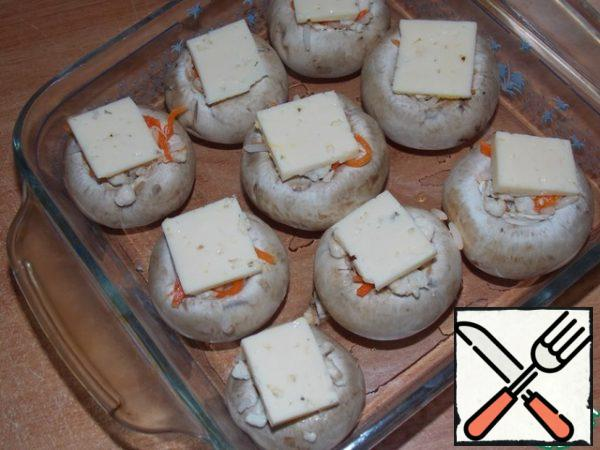 Cut the cheese into small slices. Spread on the mushrooms. Bake in a preheated oven at 180 C for 20-25 minutes.