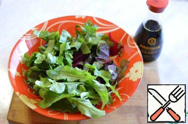 In a bowl, combine the beets and greens. Season with olive oil and soy sauce.