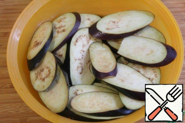 Cut the eggplants into circles, sprinkle with salt -so when frying, the eggplants will absorb less oil - and leave for 30 minutes.