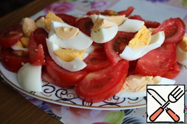 Cut large slices of tomatoes and boiled eggs. We put everything in a dish, sprinkle each layer.