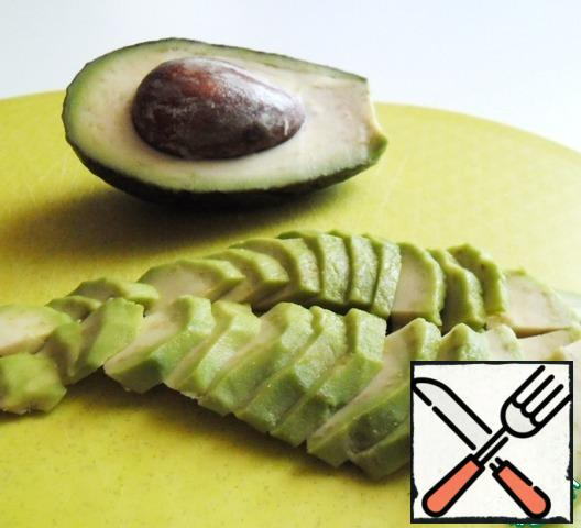 Peel the avocado and cut it into four pieces lengthwise, each part on a plate.