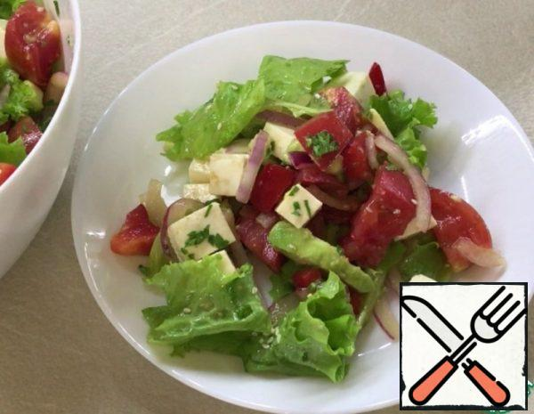 Cut the onion, squeeze out the lemon juice, add soy sauce, oregano. Leave to marinate in a separate bowl. Cut the remaining ingredients: tomatoes, bell pepper, avocado, cheese, parsley. Lettuce leaves are torn into pieces. Transfer the pickled onions to the salad bowl. The salad is dressed with sunflower oil. Stir. Sprinkle with sesame seed.