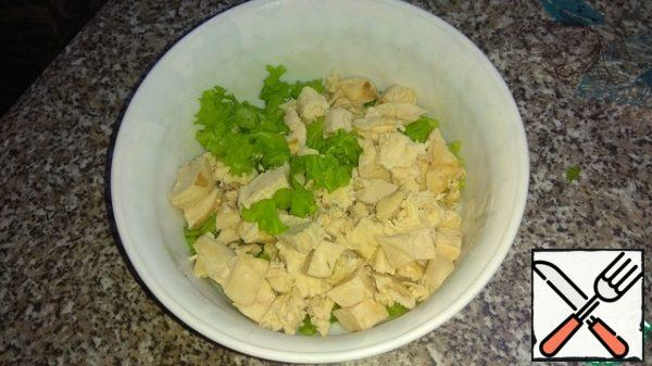Cut the lettuce leaves, add the chopped chicken fillet.