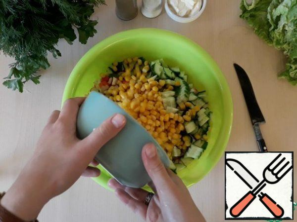 Pour everything into a large container and add the canned corn.