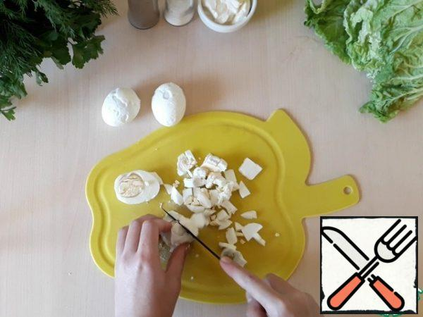Finely chop the hard-boiled chicken eggs and add them to the cucumbers with corn and crab sticks.