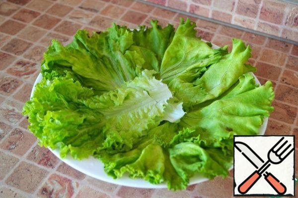Put the salad leaves on a plate.