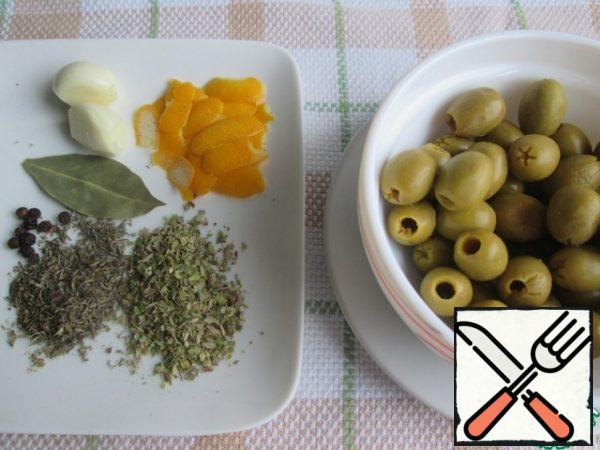 Remove the olives from the jar and drain the liquid. Remove the zest from the lemon with a vegetable peeler, in wide strips. Prepare dried herbs, Bay leaf, black pepper and garlic.