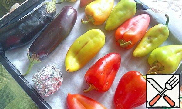 Wash the eggplants and peppers, dry them, chop them, put them on a baking sheet covered with foil, and bake them in an oven heated to 200°C until they are ready. The photo shows a lot of pepper, because I baked it at the same time for another snack.