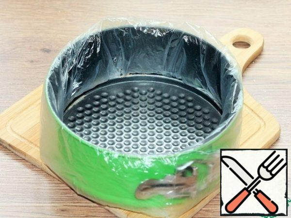 Prepare a split form f=18 cm for baking. Remove the bottom and put a transparent bag. Return the bottom of the mold to its place and cover with baking paper.