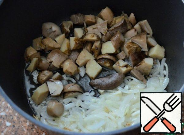 Boil the mushrooms on a sieve, use the broth for soup. Fry the onion in vegetable oil and add the chopped mushrooms.