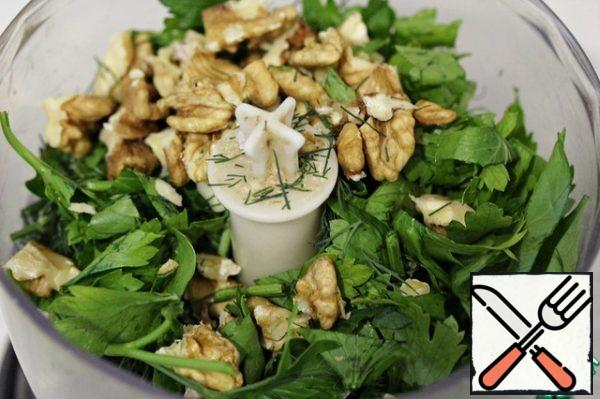 Put the dill, parsley, garlic and nuts in the bowl of a blender or food processor.
