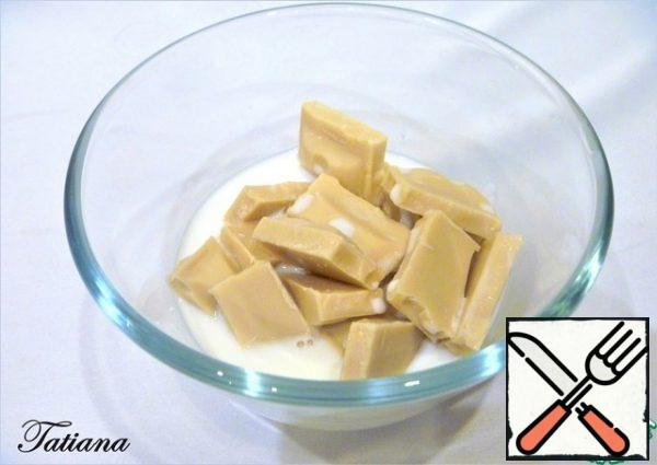 Melt white chocolate in hot milk. Let the chocolate-milk mixture cool.