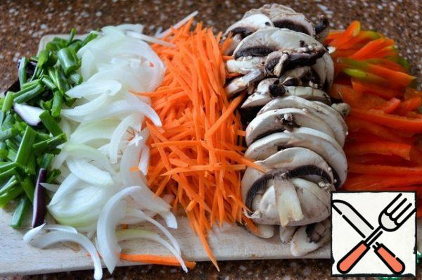 Cut into thin strips of pepper, mushrooms, onion feathers, carrots straws. The dish is prepared quickly, so the slicing should be ready.