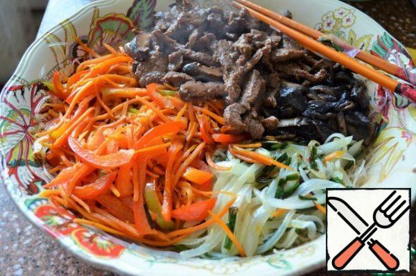 Also quickly fry the mushrooms, separately pepper and carrots, add to the salad bowl. The last to fry the meat, slightly pressing from the marinade. Put everything on the noodles.