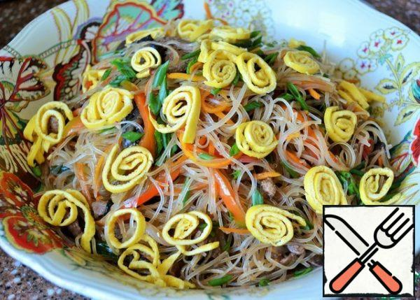 Add the dressing and gently mix everything in the salad bowl, more convenient with your hands. Garnish with yolk rolls and green onions.