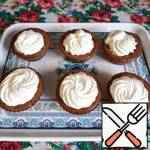 Decorate mini cheesecakes with whipped cream. Beat the cooled cream with powdered sugar until it thickens. Using a pastry bag with a nozzle, put the whipped cream on the cheesecakes.