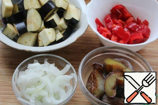Prepare the vegetables-eggplant cut into round pieces 1 cm thick and 4 parts. Cut the onion into quarters thinly. Pepper strips. Cut the plums in half.