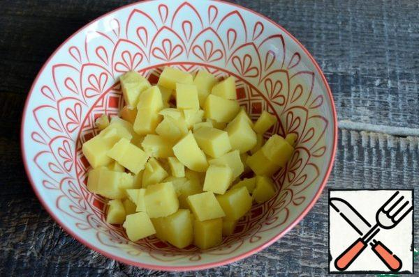 Cook potatoes in salt water, cool, and cut into medium cubes.