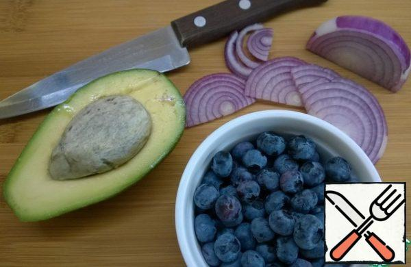 Cut the red onion into half rings. Cut the avocado into pieces and mix with the lemon juice. Wash and dry blueberries or blueberries. Cut the feta cheese into squares.