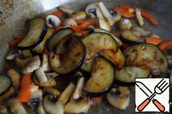 Add the ready-made eggplant to the vegetables, season everything with a mixture of soy sauce and vinegar and warm everything together in a pan for a minute.