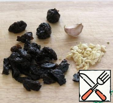 Chop the prunes and garlic.