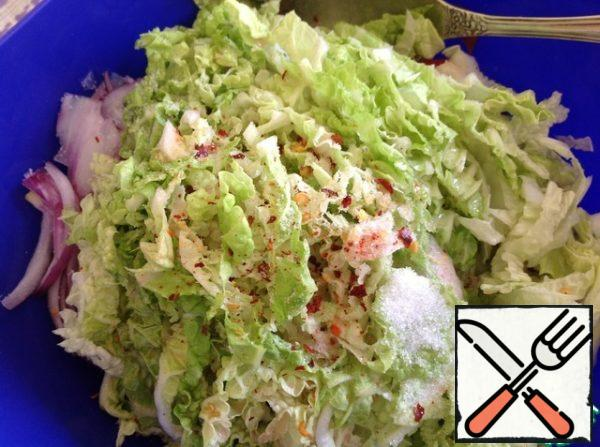 Chop the soft green part of Chinese cabbage. Add spices, oil, sugar and vinegar. Mix the salad thoroughly. When serving, cut the green onions into 5 cm long feathers and garnish the salad.