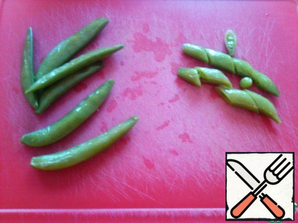 Put the pea spatulas in boiling water for 1 minute and immediately cover with cold water (if you have fresh ones). Or defrost (if frozen). And cut it diagonally, send it to the vegetables.