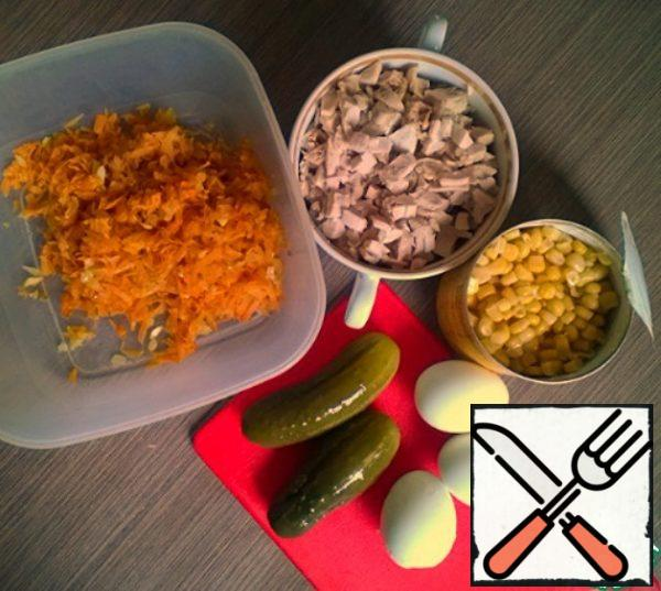 Cook and chop the eggs. Cut the cucumbers. Mix with chicken, carrots and onions, corn.