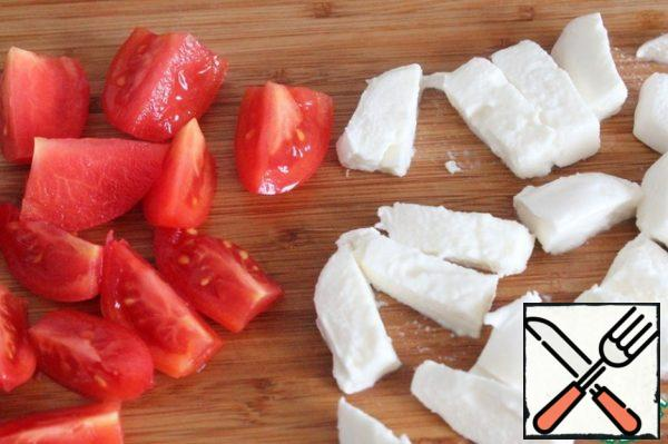 Cut the tomato and mozzarella at random.