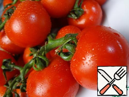 The recipe is simple. Grease the baking sheet with olive oil. Cherry tomatoes on a twig are placed on a baking sheet.
