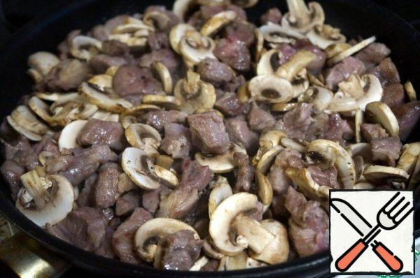 Put the mushrooms to the meat. Fry, stirring, until the mushrooms are ready.